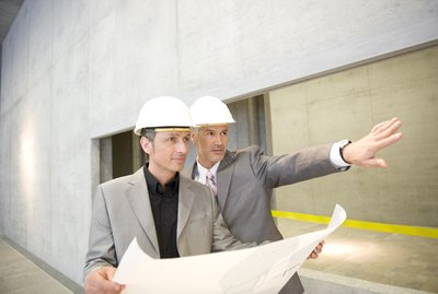 Businessmen in hard hats looking up in office building