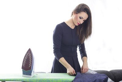 Happy young beautiful woman ironing clothes