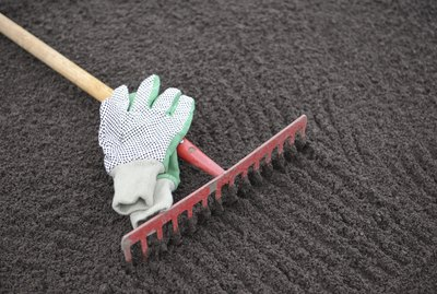 Garden rake and gloves on leveled soil