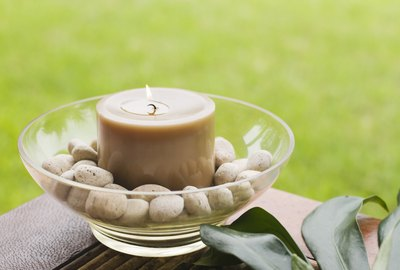Bowl with candle and pebbles on table outdoors