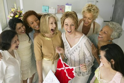 Women at gathering, laughing at woman holding up top