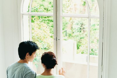 Young Couple Stand Looking Through French Windows Into Garden