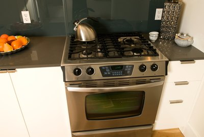 Stovetop and oven by a tray of fruit on the counter