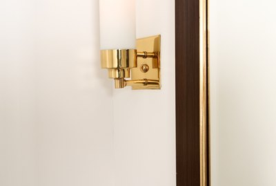 Brass light fixture on wall
