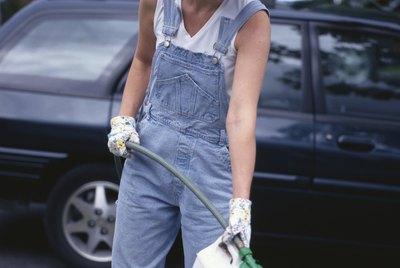Woman using fertilizer with hose in yard