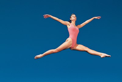 Woman in leotard leaping across sky