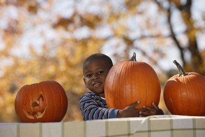 Boy embracing pumpkin