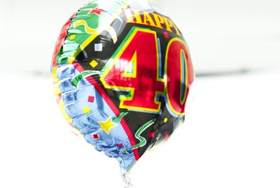 a shiny birthday message helium balloon held up by a thread