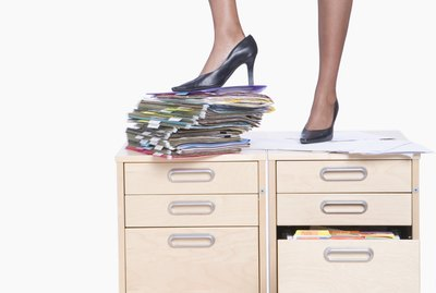Young business woman standing on filling cabinet on stack of folders, low section