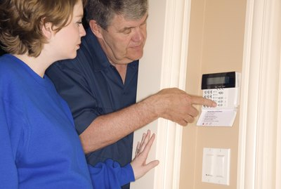Man and woman setting home alarm system