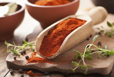 red ground paprika spice in wooden scoop and bowl