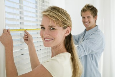 Couple measuring window blinds