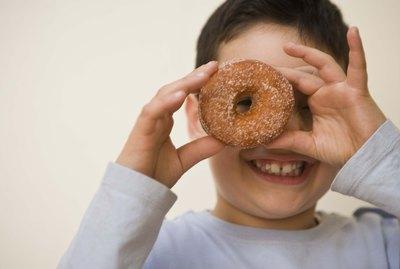 Boy looking through hole of doughnut