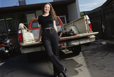 a young caucasian woman in black pants and shirt is leaning against the tailgate of a pickup truck with her black dog lying in the truck bed