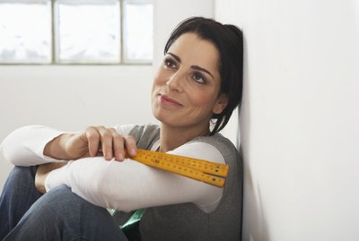 Woman leaning against wall holding measuring tape