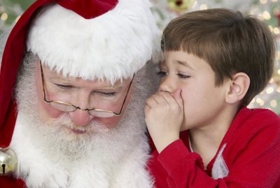 Young Boy Whispers Into Father Christmas' Ear