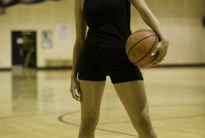 Young woman holding basketball posing in sports hall, portrait