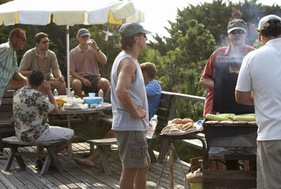 Group of men having barbecue on decking