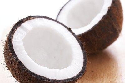 Split coconut on wooden board, close-up