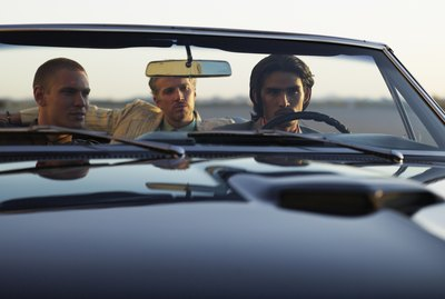 3 men in a car in desert