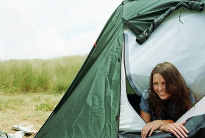 Young woman lying in tent opening, looking away, smiling