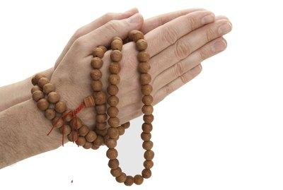 Man holding Buddhist prayer beads, close-up of hands