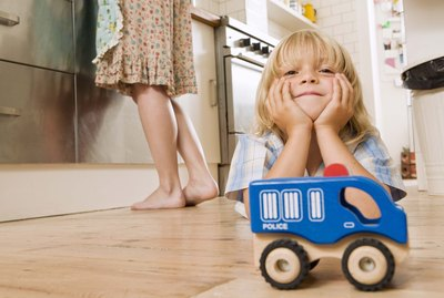 Boy on kitchen floor with toy car