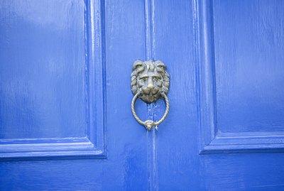 Metal lion's head knocker on blue-painted front door