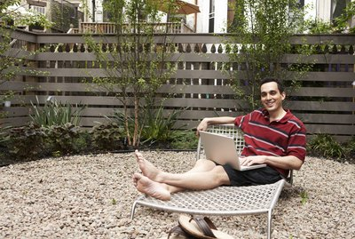 Relaxing on lounge chairs in urban backyard