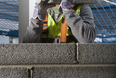 Construction worker building cinderblock wall