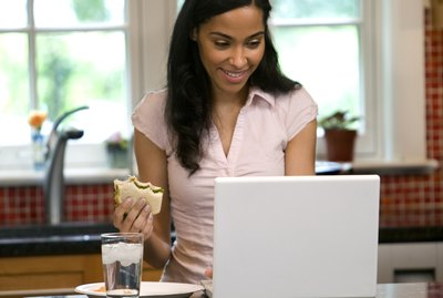 Woman on laptop in kitchen, eating snack