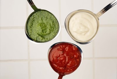 Ladles of tomato , pesto and mornay sauces