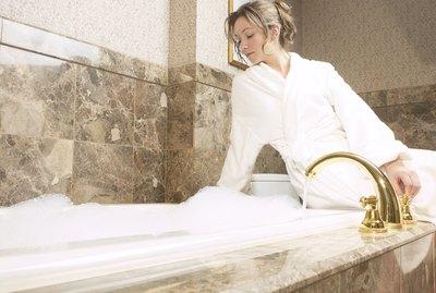 Woman sitting by bubble bath