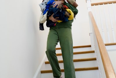 Woman carrying laundry down stairs