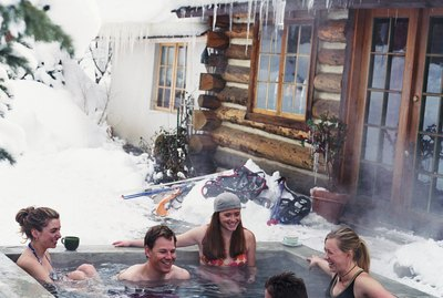 Group of young adults in outdoor hot tub surrounded by snow