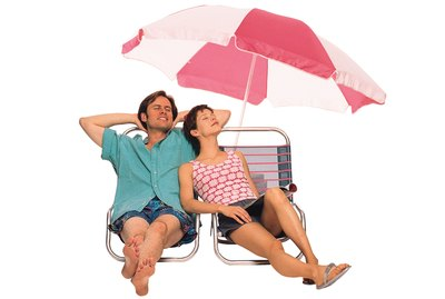 Couple reclining on lounge chairs under beach umbrella