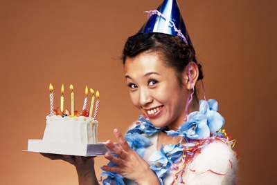 Young Woman Holding a Birthday Cake, Side View, Looking at Camera