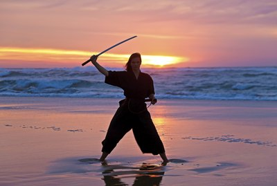 Young samurai women with Japanese sword(Katana) at sunset on the