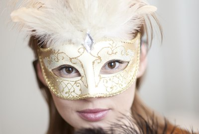 Portrait of young woman wearing ornate mask