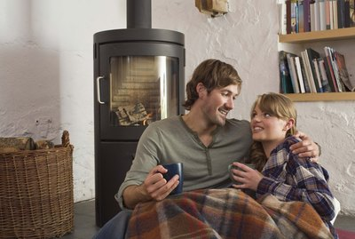 Couple snuggling by wood stove indoors