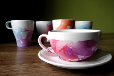 DIY Nail polish marbled mugs on table.