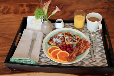 breakfast tray with stuffed french toast, bacon and orange slices