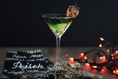 green caramel apple martini garnished with shrunken head