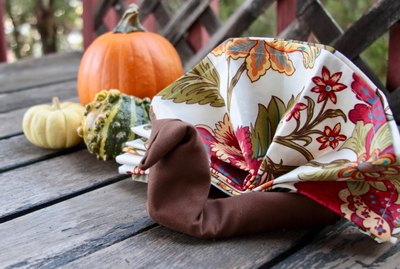 Napkins folded in the shape of a turkey for Thanksgiving decor.