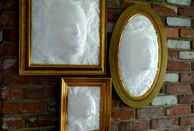 3 separate picture frames each with a cheesecloth ghost head