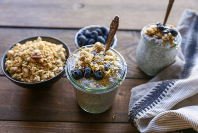 Two jars of chia seed pudding topped with blueberries and granola