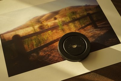 A camera body cap-turned pinhole lens sits on a photograph of a rural fence and mountain scene.