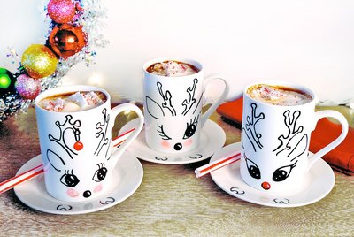 Three white mugs with hand drawn reindeer faces, full of hot chocolate.