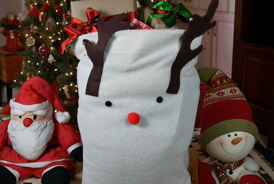 Sherpa Reindeer bag beside Christmas tree
