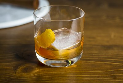 An Old Fashioned cocktail on a wood table